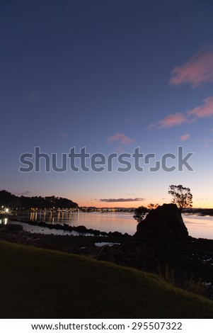 A lovely night seen just as the town of Whakatane, New Zealand turns on its lights. Peaceful and serene, the people are settled in for a long chilly, winter evening. Lovely photo for many purposes. - stock photo