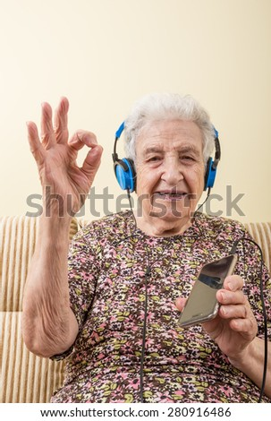 a lovely senior woman listening music (with smart phone / ipod) - stock photo