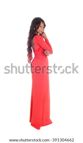 A lovely slim African American woman in a long red dress and curly longblack hair standing in profile isolated for white background. - stock photo