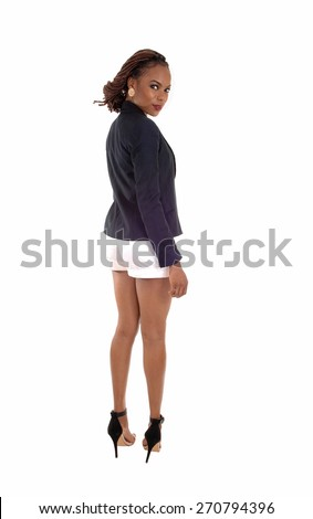 A lovely slim young African American woman in a dark blue jacket and white shorts, standing from back, isolated for white background.  - stock photo
