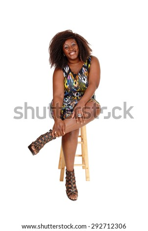 A lovely smiling African American woman sitting in a colourful dress on a chair, isolated for white background. - stock photo