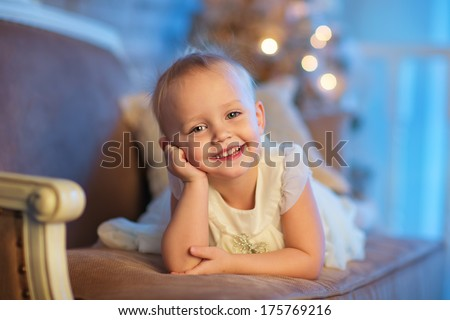 A lovely 3 year old girl in a beautiful white dress lying on a sofa in front of the decorated Christmas tree - stock photo