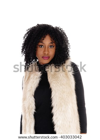 A lovely young African American woman in a black dress and a whitefur coat looking sad into the camera, isolated for white background. - stock photo