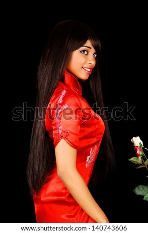 A lovely young black woman in a red chinese dress for black background in profile with her long brunette hair.  - stock photo