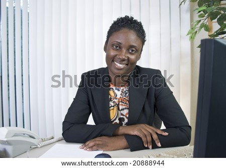 A lovely young Black woman in an office environment smiling a kind, friendly smile. - stock photo