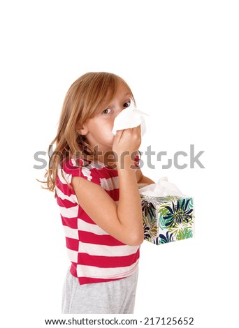 A lovely young blond girl holding a tissue on her running nose, isolated for white background.  - stock photo
