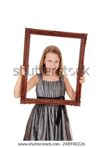 A lovely young girl in a grey dress holding a picture frame in front of her, isolated on white background.
