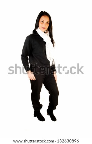 A lovely young teenage girl in her school uniform, black top and long black pants, standing in the studio for white background.