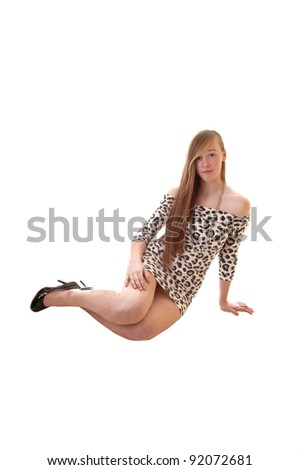 A lovely young teenage girl sitting on the floor in a leopard print dress, her long brunette hair falling down, in heels for white background. - stock photo