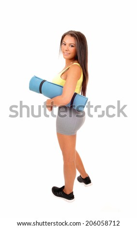 A lovely young teenager girl in exercise clothing having a yoga matt under her arm, in profile isolated on white background.  - stock photo