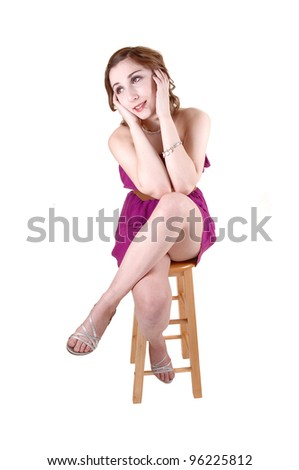 A lovely young teenager sitting in a pink dress on a chair, her legs grossed and her hands holding her face, for white background. - stock photo