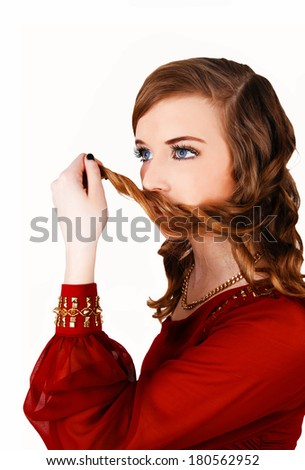 A lovely young woman in a red dress holding some hair on her mouth, standing for white background.  - stock photo