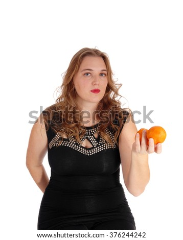 A lovely young woman in an black dress standing isolated for whitebackground holding two oranges. - stock photo