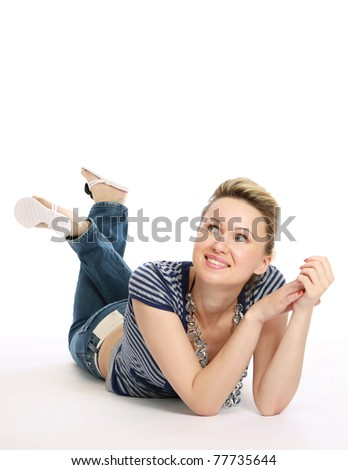 A lovely young woman lying on the floor, looking up - stock photo