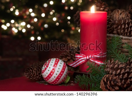 A Lovey Christmas Still Life of a Lit Red Candle with an Ornament and Pine Cones with a Christmas Tree in the Background with Room for your Words or Text. - stock photo
