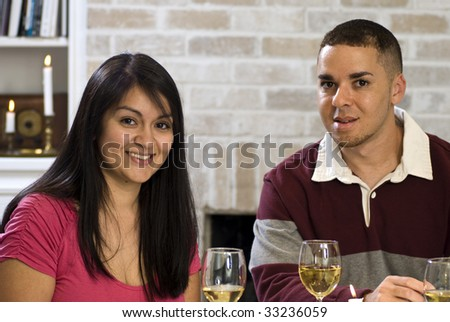 A lovey Hispanic woman and a friend enjoying smiling at the camera over glasses of wine. - stock photo