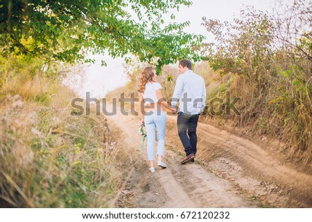 A loving couple are standing in the field road with trees at sunset, holding hands and kissing each other. Bright sunlight shines. Around the greens. Walk on the nature. Country style.