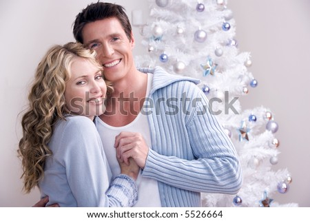 A loving couple in front of the christmas tree - stock photo