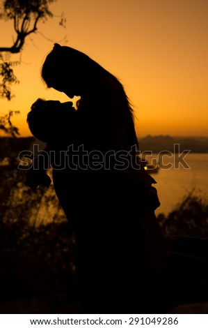a loving couple shown as silhouette against sunset - stock photo