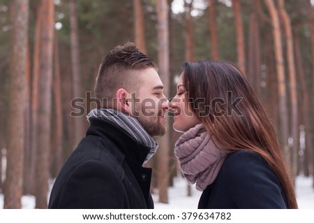 A loving couple walking in winter park with pine trees.
