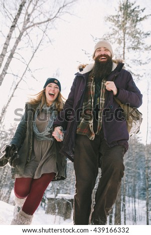 A loving happy young couple emotionally runs in the winter woods. Rustic style - stock photo