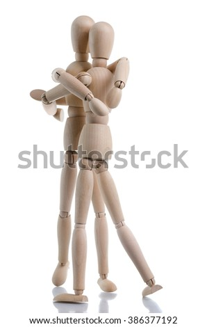 A loving hug is shared between two wooden characters, isolated on a white background. - stock photo
