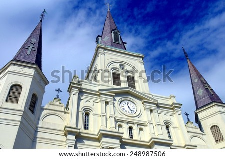A low, abstract angle of Saint Louis Cathedral on Jackson Square in the New Orleans French Quarter with a dramatic blue sky with white clouds. - stock photo