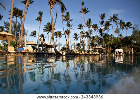 A low angle view from inside a pool at a luxurious resort. - stock photo