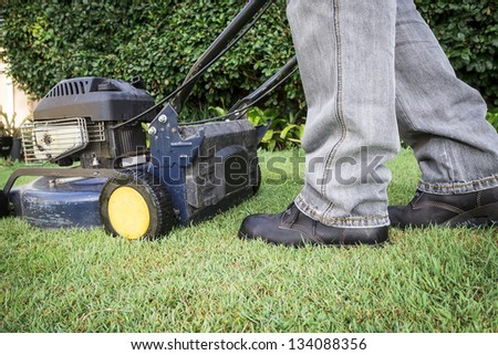A low angle view of a man preparing for lawn mowing - stock photo