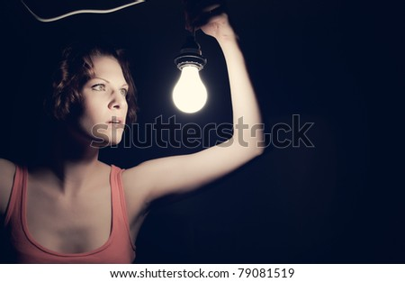 A low-key portrait of a girl holding a light. - stock photo