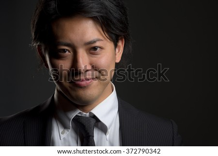 A low key portrait of a young Japanese man in a business suit with a hint of a smile on his face. - stock photo