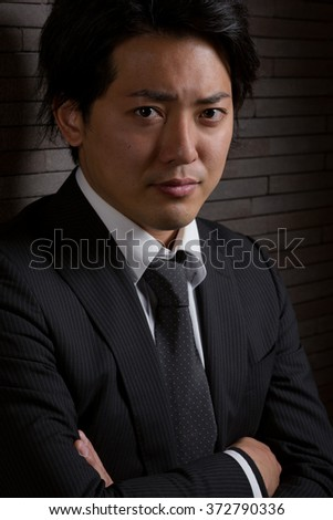 A low key portrait of a young Japanese man in a business suit with a serious expression on his face. - stock photo