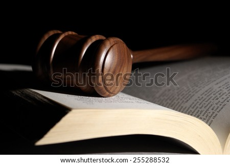 A low key shot of a gavel on a book. - stock photo