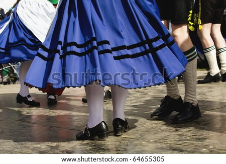 A low perspective of tradionally dressed dancers at an Oktoberfest even in fall. - stock photo
