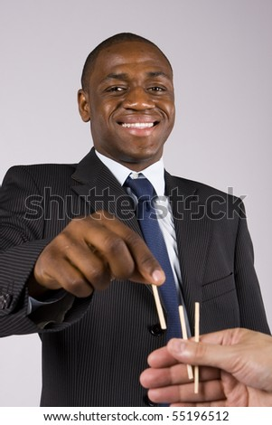 A lucky business man choosing a straw - Focus on the head - stock photo