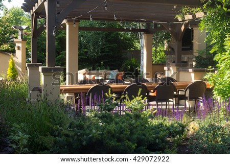 A luxurious backyard setting for entertaining guests surrounded by perennials. - stock photo