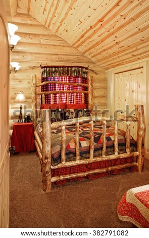A luxurious bedroom, with a queen sized bed, in a modern log cabin in the mountains. - stock photo