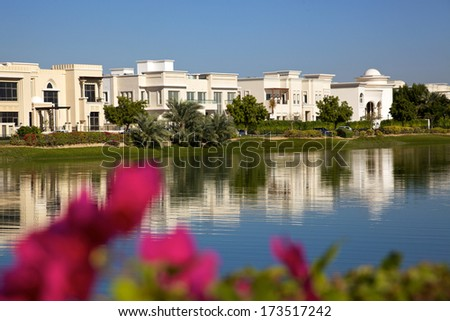 A luxurious residential area of Dubai, with modern tower blocks in the background and soft-focus bougainvillea in the foreground. - stock photo