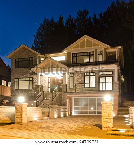 A luxury house with big driveway and the original garage doors in suburbs at dusk in Vancouver, Canada - stock photo