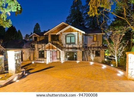 A luxury house with big driveway  in suburbs at dusk in Vancouver, Canada - stock photo