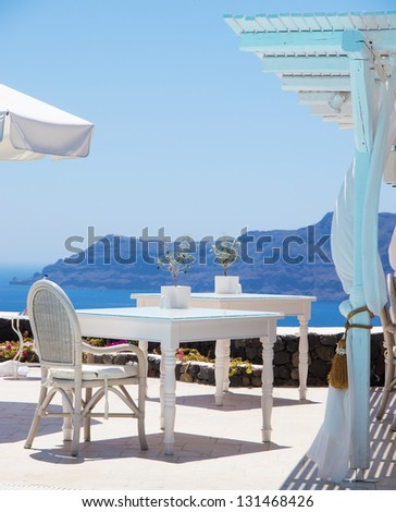 A luxury restaurant situated in the town of oia on the greek island of santorini with a view of volcano in the distance. - stock photo