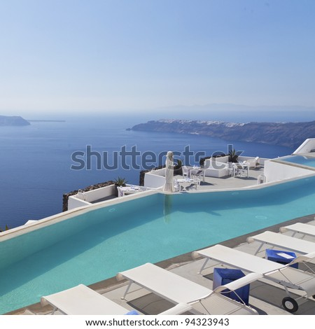 A luxury swimming pool situated in the town of imerovigli on the greek island of santorini with a view of oia in the distance.