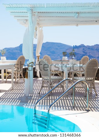 A luxury swimming pool situated in the town of oia on the greek island of santorini with a view of volcano in the distance. - stock photo