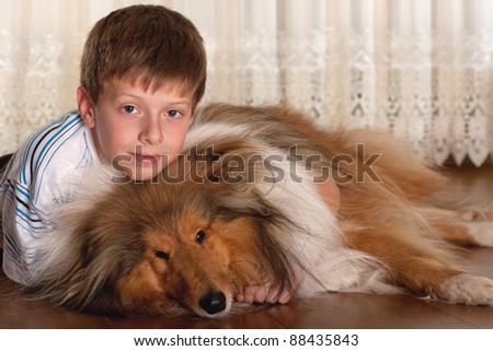 A lying on the floor serious boy is hugging his dog - stock photo