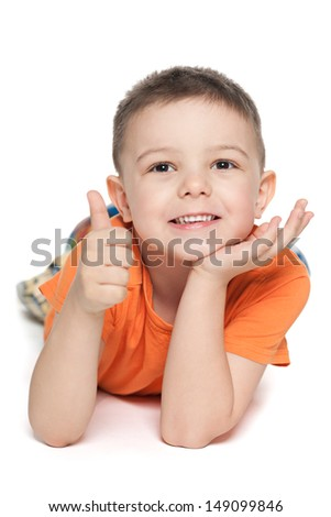 A lying on the white background little boy holds his thumb up