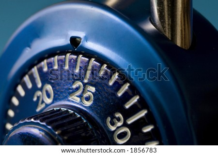 A macro (close up) image of a blue combination lock.  The number 25 is just past the tumbler and in sharp focus. - stock photo