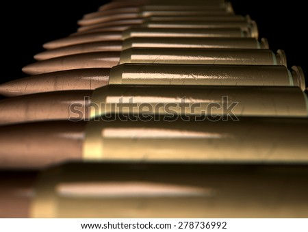 A macro close up view of a row of regular scratched brass and copper bullets on an isolated black background