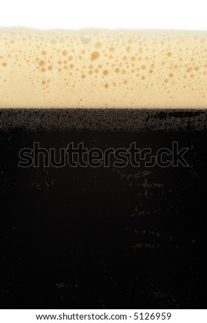 A macro image of a glass of stout beer or bitter. - stock photo
