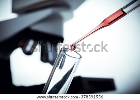 A macro of a pipette adding a drop of fluid to one of several cylindrical phials,  background is a microscope. - stock photo