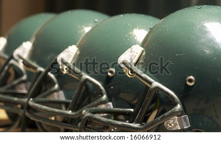 a macro of few football helmet on bench